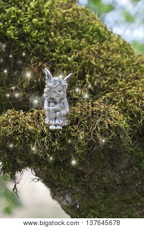 Small fairy sitting on mossy branch with sparkles of light glowing around her.
