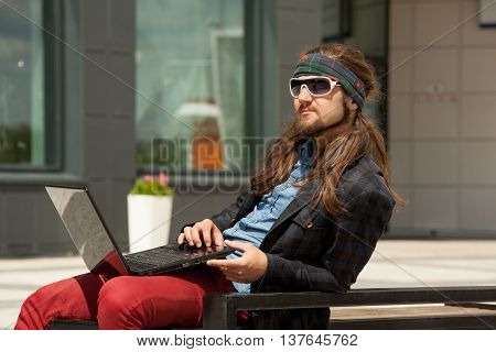 Young hipster fashion guy with beard. The man with a laptop and headphones sitting on a bench in the city and working.