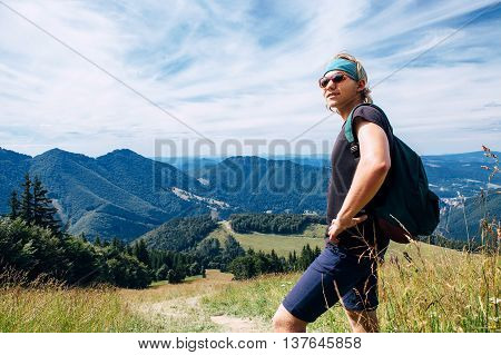 Young man travels in mountains halting for a breather