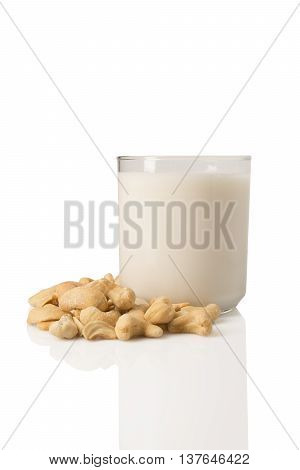 A glass of cashew milk with a pile of cashews around it.