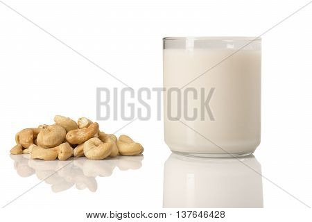 A glass of cashew milk with a pile of cashews next to it.