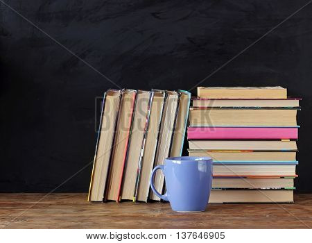 Books in stacks and Cup on the table in the background of a school blackboard. Back to school.