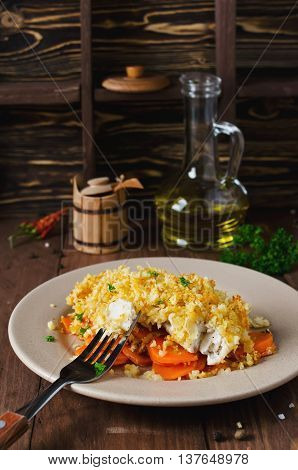 Oven-roasted fish fillet with carrots under a bread crust. For garnish white rice