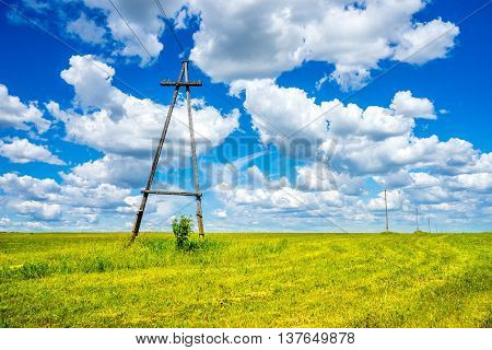 Electric poles on a field and cloudy sky