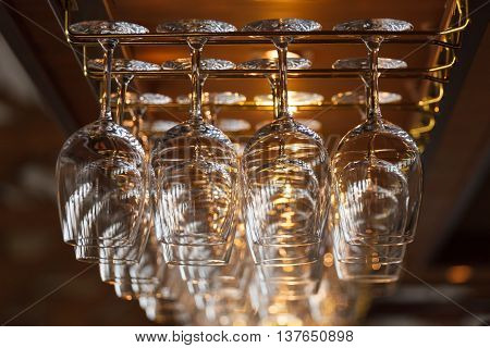 different glasses hanging over the bar. Soft focus