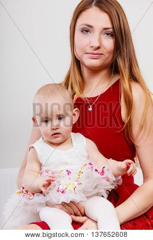 Single parent concept. Young elegant mother with baby girl in princess ballerina dress on mommy knees. Parenthood.