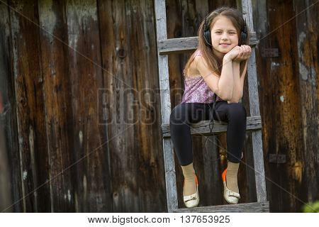 Little naughty girl with headphones sitting on a wooden stepladder in the village outdoors.
