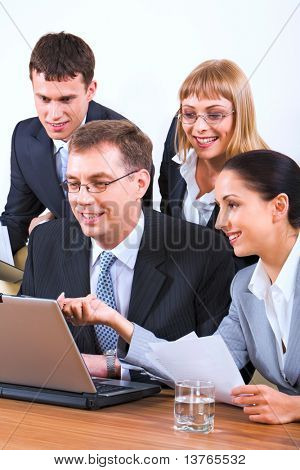 Portrait of young businesswoman holding documents showing to the monitor of laptop and three businesspeople gathered together around the table with the laptop and glass of water on it