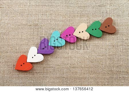 Orange, white, purple, turquoise, magenta, beige, green, brown wooden hearts-buttons on raw light gay linen cloth