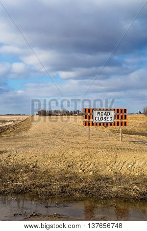 Road closed sign on a dirt road.