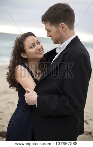 Engaged asian female and caucasian male in love in a romantic beach while wearing a dress and suit