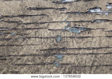 Peeling paint on an old wooden table top.