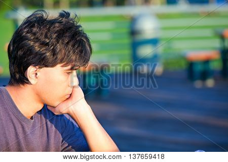 Young man sitting at park deep in thought. Sad or unhappy