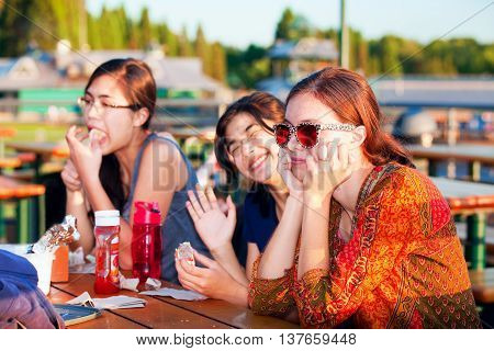 Three young women eating hotdogs together at lakeside