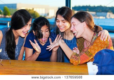 Four young women sitting together enjoying new ring on firend's finger