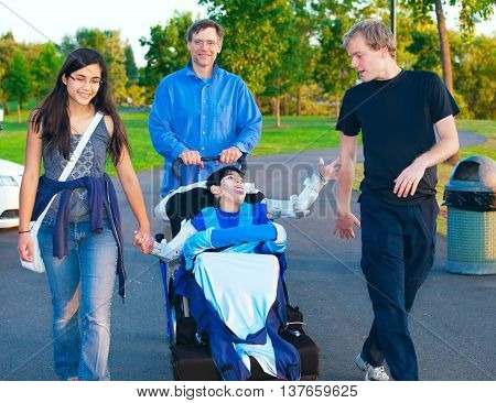 Disabled boy in wheelchair walking at park together with family and friends
