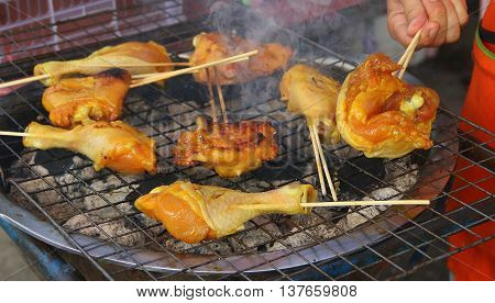 pieces of chicken cooking on smoking barbecue grill, hand of man seen picking up one of the pieces with a fork.
