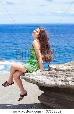 Beautiful biracial teen Asian Caucasian girl sitting on rocky ledge overlooking blue ocean off the coast of Hawaii on sunny day
