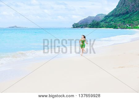 Beautiful biracial Asian Caucasian teen girl in green dress running on empty secluded Hawaiian beach