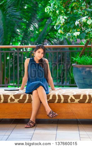 Beautiful biracial Asian Caucasian teen girl sitting on cushioned bench outdoors in Hawaii with tropical scenery in background