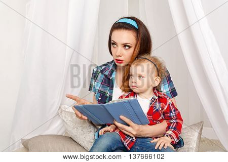 Mother and daughter read the e-book. Fairy tales. Mother explains All Read. Young mother and baby daughter hugging. Girls dressed in plaid shirt. Family education