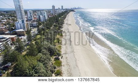 Aerial view of Burleigh beach and surrounds at sunrise, with morning sun rise glistening off the ocean. Gold Coast, Australia