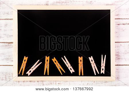 Blank Blackboard And Orange Clothes Peg On Wooden Table.template Mock Up For Adding Your Design And