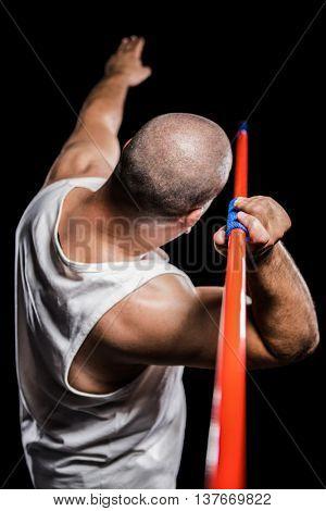Rear view of athlete preparing to throw javelin on black background