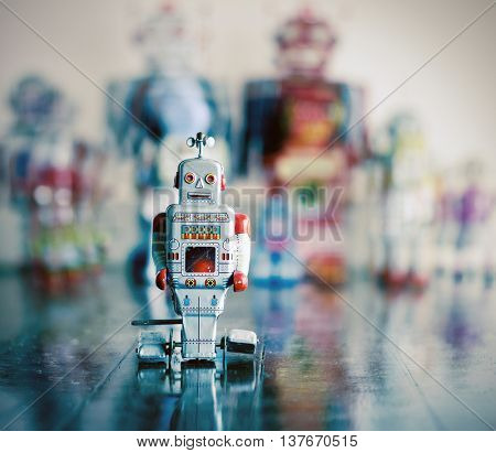 little silver robot toy on wooden floor