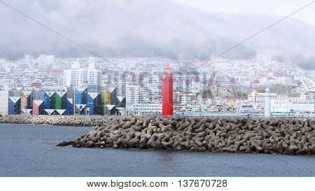 Busan South Korea - March 24th 2016: Busan beacon in the western part of island Yeongdo in a morning fog with a kind on a city.
