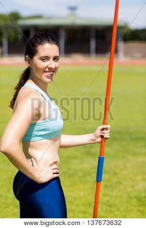 Portrait of female athlete standing with javelin in a stadium