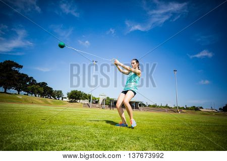 Athlete performing a hammer throw in stadium