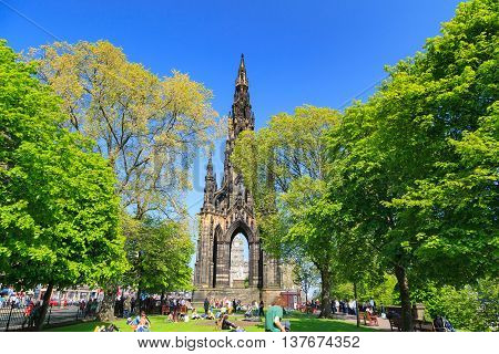 EDINBURGH - MAY 29 2016: Princes Street garden with Scott Monument full of people in a sunny summer day on 29th May 2016