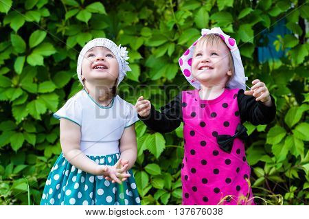 cute children looking up plaing outdoors on green