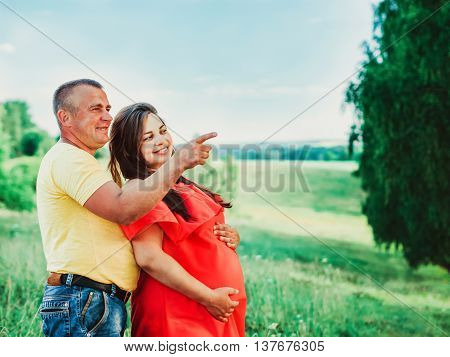 Pregnant beautiful woman in red dress and her husband with hands on belly outdoors. Man embraces from behind belly pregnant wife and shows his finger to the side