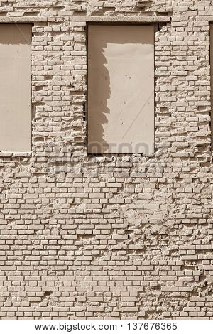 the old textured brick surface of beige color for a background and window niches on a wall