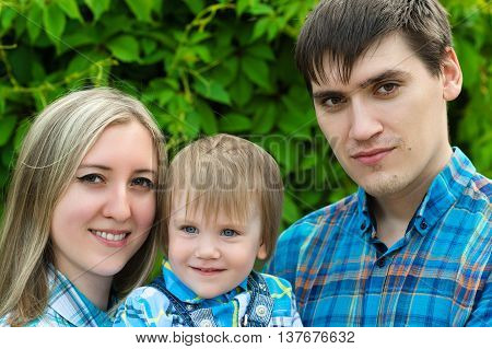 portrait happy family on background green hedge