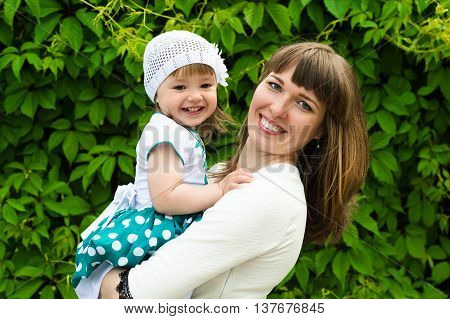 portrait smiling mother with a daughter on hands