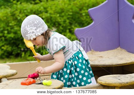 little girl child playing in the sandbox on the playground