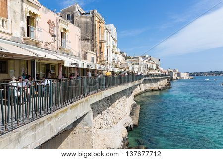 SIRACUSA ITALY - MAY 18: Tourists and restaurants near the harbor of Syracusa on May 18 2016 at the island Sicily Italy