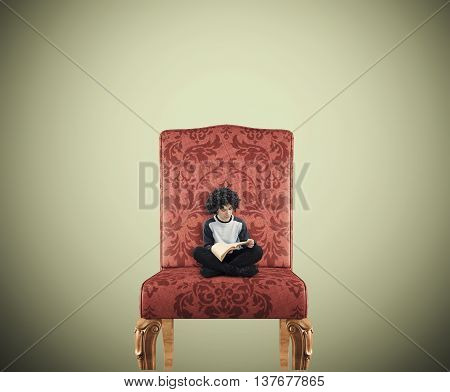 Teenager reading a book on a huge chair