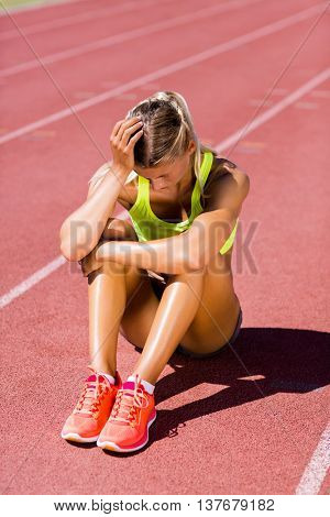 Upset female athlete sitting on running track on a sunny day