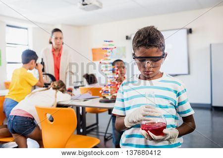 Pupil looking at beaker in science lesson