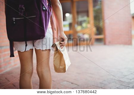 Rear view of a schoolgirl with her lunch meal bag