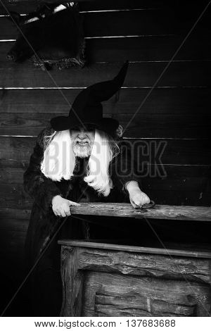 Brutal druid old man with long silver hair and beard in Halloween hat opens vintage wooden chest black and white on log house background
