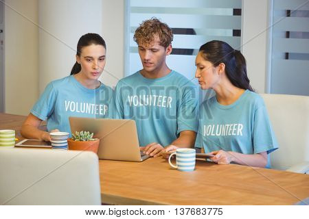 Volunteers using a laptop in the office