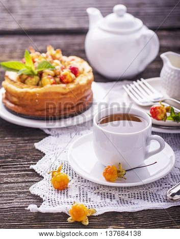 Homemade breakfast. Fresh cheesecake with berries ripe northern rare cloudberries on a wooden background with vintage handmade embroidered tablecloth. Served with white ceramic dishes