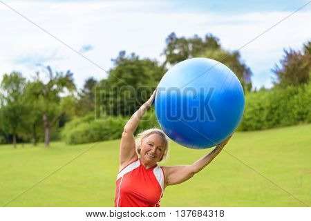 Happy Senior Woman With Stability Ball Over Head