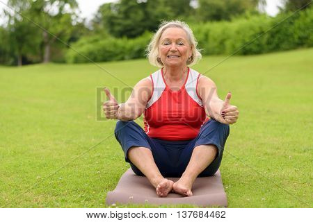 Smiling Senior Woman On Yoga Mat With Thumbs Up