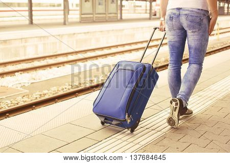 Womans legs with suitcase at the train station
